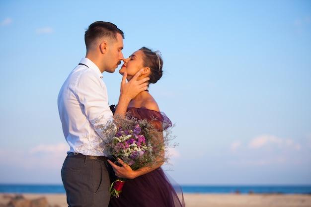 Молодая романтичная пара отдыхает на пляже, наблюдая закат
