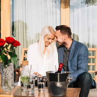 氷のバケツのワインボトルでテーブルの後ろに座っている若いロマンチックなカップル