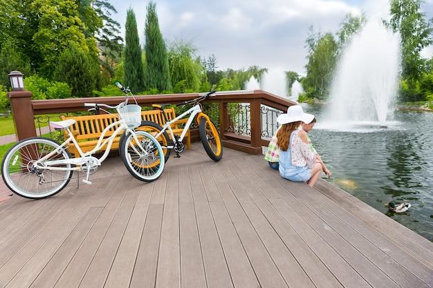 분수와 다른 나무가 배경에 있는 공원 연못에서 자전거를 타고 오리에게 먹이를 준 후 나무 데크에 앉아 있는 젊은 로맨틱 커플