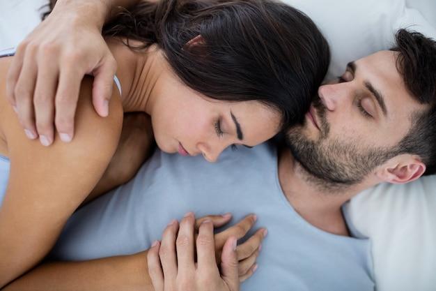 Young romantic couple sleeping on bedâin bedroom