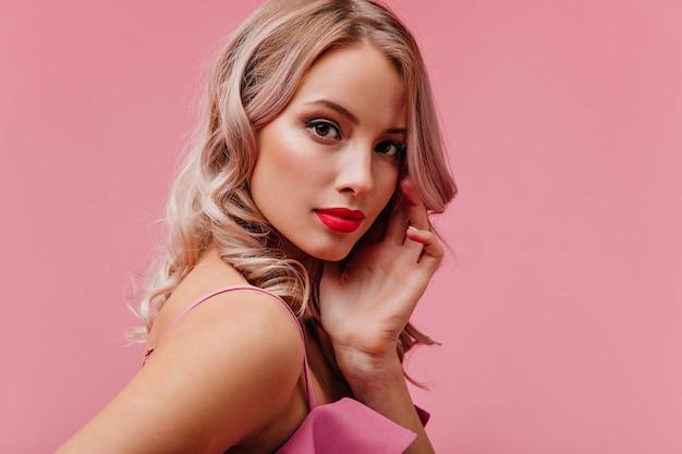 ピンクの孤立した壁に肖像画のポーズをとって明るいメイクでモデルの外観の若いロマンチックなかわいいブロンドの女性