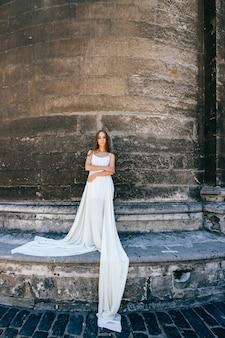 石の古代の壁にポーズをとって長い白いドレスを着た若いロマンチックでエレガントな女の子