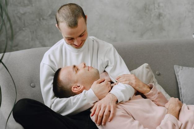 ソファで抱きしめたりリラックスしたりして一日を過ごす若いロマンチックな同性愛者のカップル