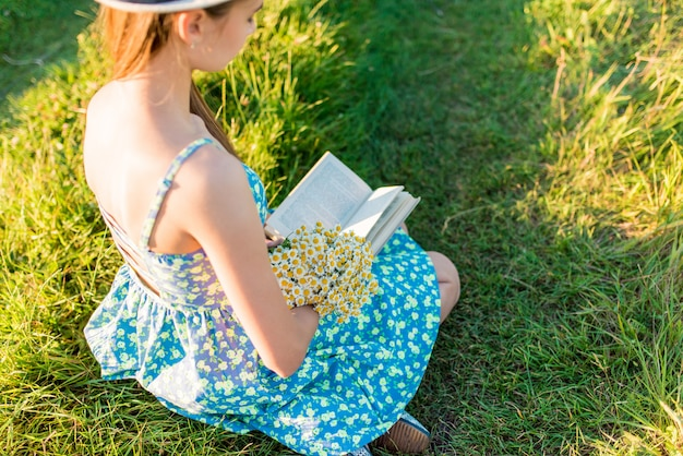 Молодая романтическая девушка в голубом платье и шляпе, сидя с открытой книгой на закате
