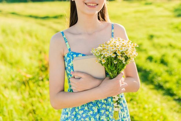 Молодая романтичная девушка в голубом платье с открытой книгой на заходе солнца.
