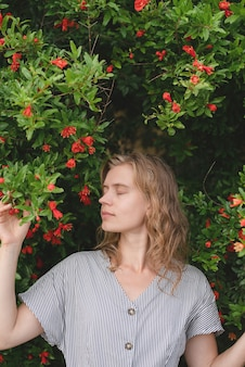 Young romantic lady enjoying blossom of flowers