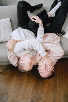 ソファで抱きしめたりリラックスしたりして一日を過ごす若いロマンチックなlgbtqカップル。異なる家族のライフスタイルの概念。