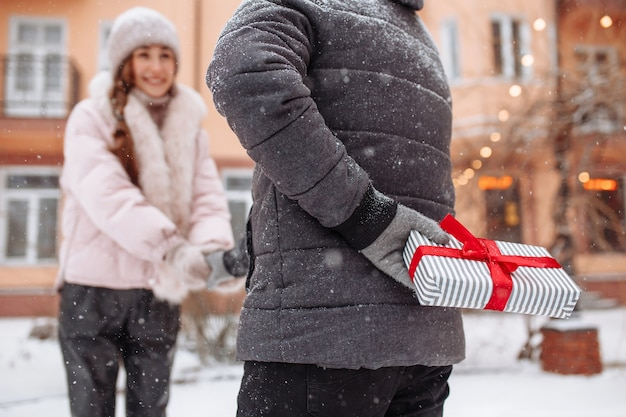 Young romantic man is about to give a present to his girlfriend for a valentine's day. male holding a gift box with a red bow behind his back on a snowy winter day.