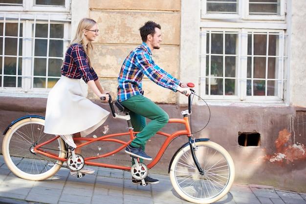 若いロマンチックなペア、男性と女性が舗装された歩道に沿ってタンデムダブル赤い自転車を一緒にサイクリング