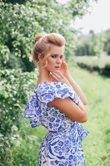 Young romantic woman in blue flower dress with makeup and hairstyle in green summer garden