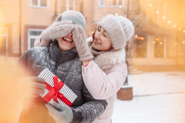 젊은 낭만적 인 여성이 모직 장갑을 낀 손으로 남자 친구의 눈을 감고 겨울 눈 덮인 공원에서 깜짝 놀라게합니다. 웃는 남자는 붉은 활과 선물 상자를 보유하고있다. 발렌타인 데이 개념.