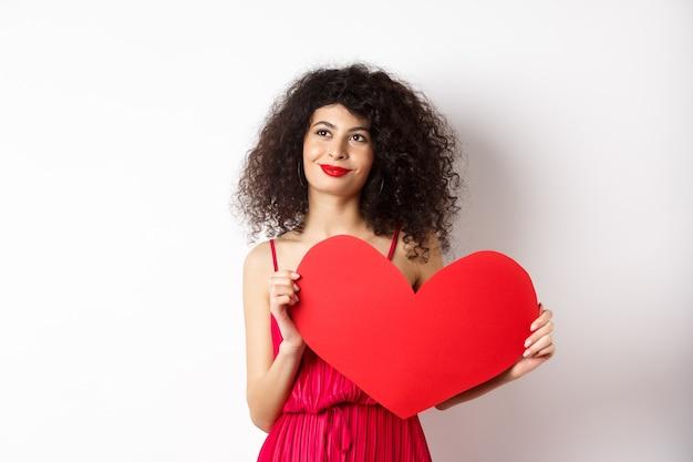 Молодая романтическая женщина мечтает о любви в день святого валентина, ищет вторую половинку, держит вырез в большом красном сердце и задумчиво смотрит влево, на белом фоне.