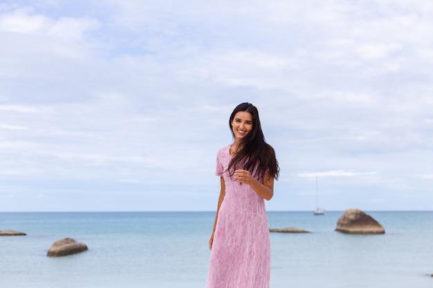 해변에서 드레스에 긴 검은 머리를 가진 젊은 낭만적 인 여자가 웃고 혼자 좋은 시간을 보내고 웃고