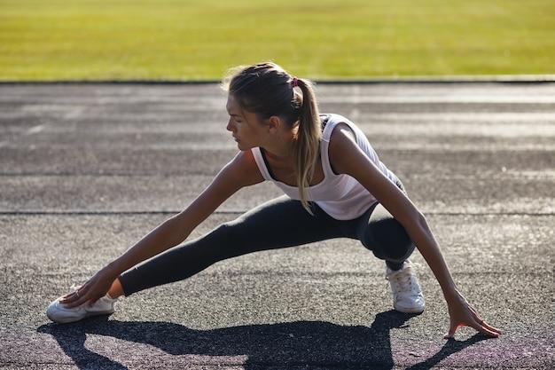 若いランナーは屋外で運動する前にストレッチする女性にフィット
