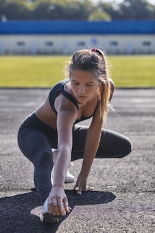Young runner fit woman streching before exercises outdoors