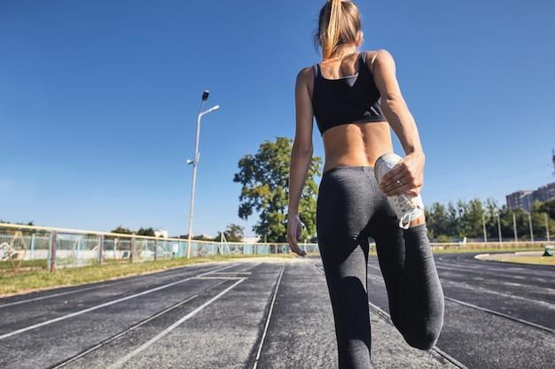 Молодой бегун подходит женщине, растягивая перед упражнениями на открытом воздухе