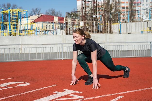 Молодой бегун в спортивной одежде готовится к спринту на стартовой линии на красной дорожке стадиона в яркий солнечный день.
