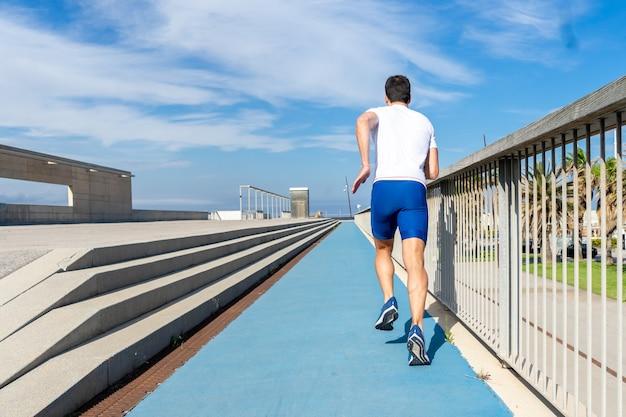 Молодой бегун в синих брюках и белой футболке работает на солнце по синей дорожке. концепция мотивации, карьера