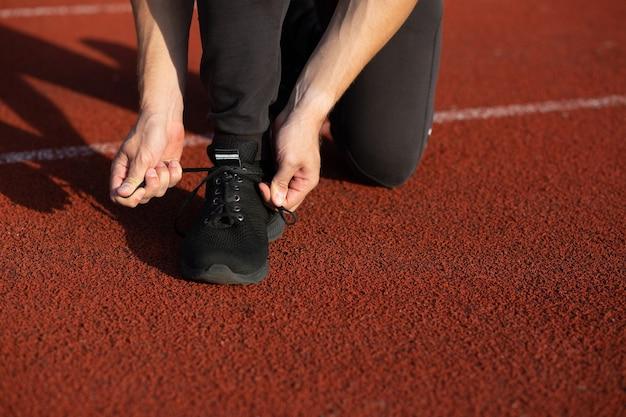 Молодой бегун завязывает шнурки на беговой дорожке. снимок крупным планом