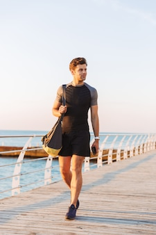 Young runner man in tracksuit with sporty bag walking along pier or boardwalk at seaside, in morning and holding smartphone