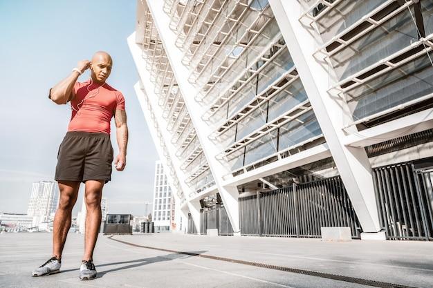 젊은 주자. 거기 운동을하는 동안 경기장 근처에 서있는 즐거운 아프리카 계 미국인 남자