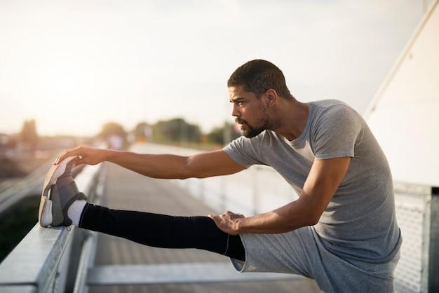 Молодой спортсмен-бегун, растягивая ноги и разогреваясь для бега