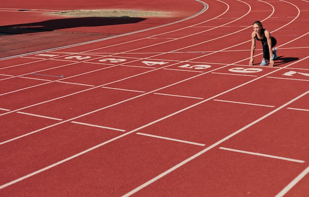 Молодая женщина бегун в спортивной одежде готовится к запуску спринта на старте на дорожке стадиона с красным покрытием в яркий солнечный день