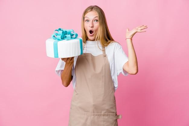 Молодая русская женщина-пекарь, держащая восхитительный торт, празднует победу или успех, он удивлен и шокирован.