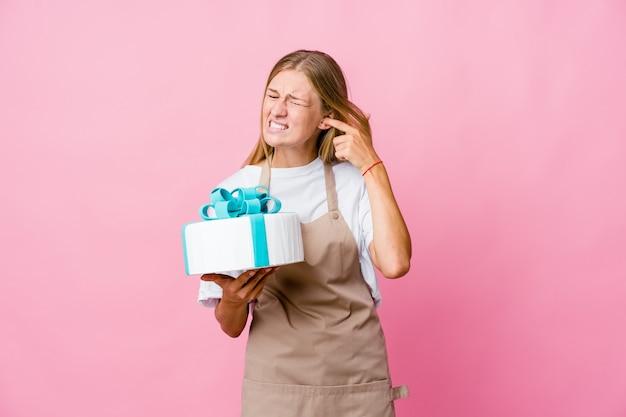 手で耳を覆うおいしいケーキを保持している若いロシアのパン屋の女性。