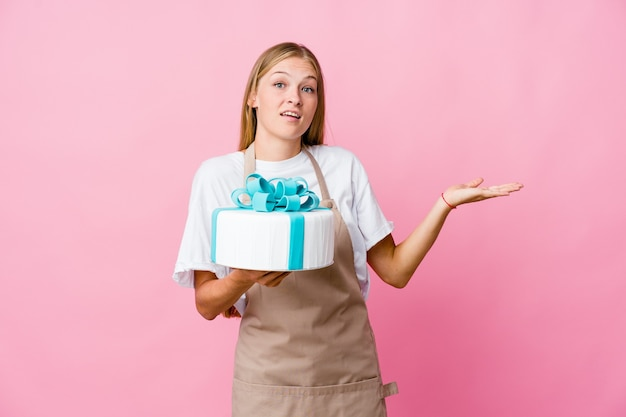 의심과 의심 제스처에 어깨를 shrugging 맛있는 케이크를 들고 젊은 러시아 베이커 여자