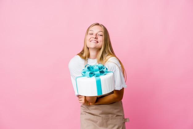 Молодая русская женщина-пекарь, держащая вкусный торт, смеется и веселится