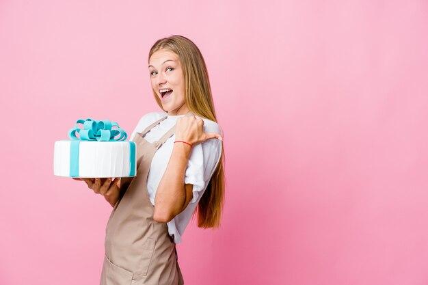 엄지 손가락으로 맛있는 케이크 포인트를 들고 웃고 평온한 젊은 러시아 베이커 여자.