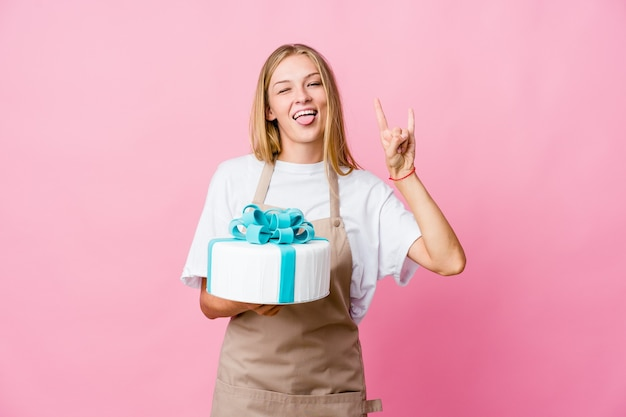 革命の概念として角のジェスチャーを示すおいしいケーキを保持している若いロシアのパン屋の女性。