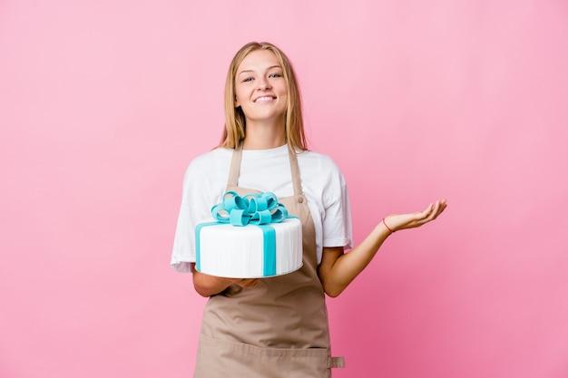 Молодая русская женщина пекаря держит вкусный торт, показывая долгожданное выражение.