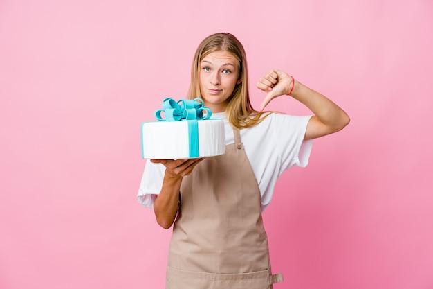 Молодая русская женщина-пекарь держит вкусный торт, показывая пальцы вверх и вниз, трудно выбрать концепцию