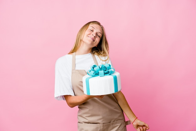 Young russian baker woman holding a delicious cake dancing and having fun.