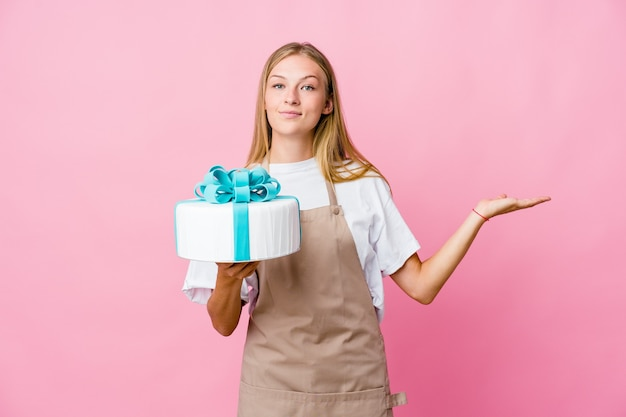 Young russian baker woman holding a delicious cake makes scale with arms, feels happy and confident