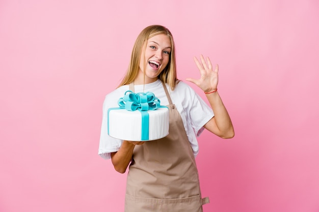 Young russian baker woman holding a delicious cake showing number ten with hands.