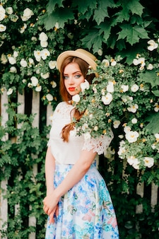 Young russian beauty. attractive girl in vintage retro long skirt, white old fashioned top and curly red hair and straw hat posing for camera with fence and green trees