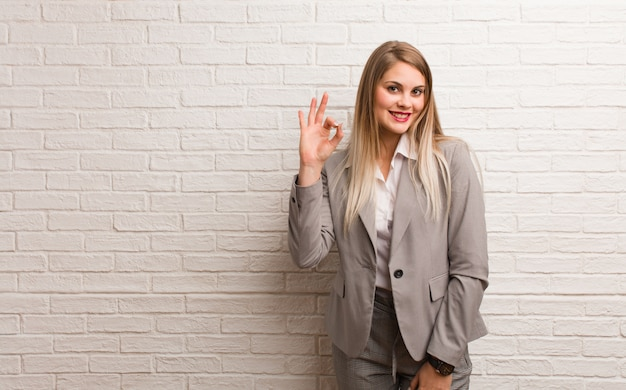 Young russian business woman cheerful and confident doing ok gesture