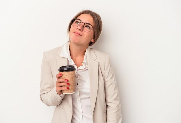 目標と目的を達成することを夢見て白い背景で隔離の紙幣を保持している若いロシアのビジネス女性