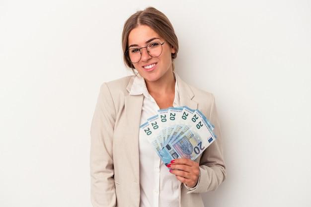 幸せ、笑顔、陽気な白い背景で隔離の紙幣を保持している若いロシアのビジネス女性。