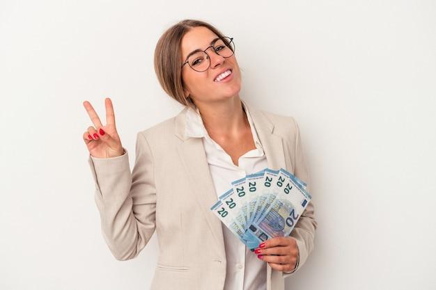 白い背景に分離された紙幣を持っている若いロシアのビジネス女性は、指で平和のシンボルを喜んで気楽に示しています。