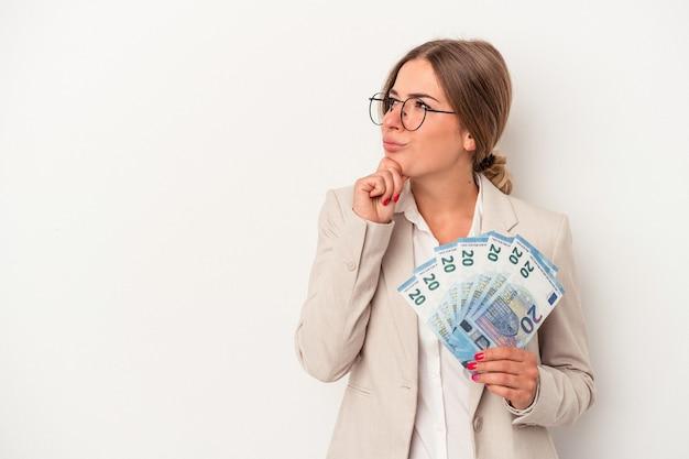 疑わしいと懐疑的な表現で横向きに白い背景で隔離の紙幣を保持している若いロシアのビジネス女性。