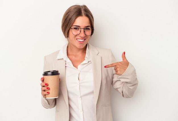 誇りと自信を持って、シャツのコピースペースを手で指している白い背景の人に分離された紙幣を保持している若いロシアのビジネス女性