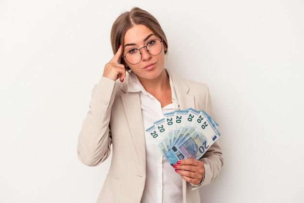 指で寺院を指して、白い背景に分離された紙幣を保持している若いロシアのビジネス女性は、タスクに焦点を当てて考えています。