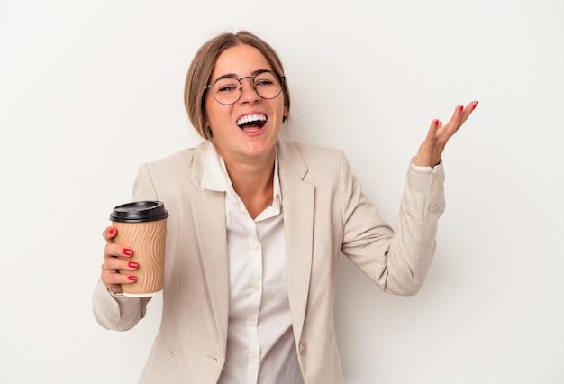 白い背景で隔離の紙幣を保持している若いロシアのビジネス女性は、嬉しい驚きを受け取り、興奮し、手を上げます。