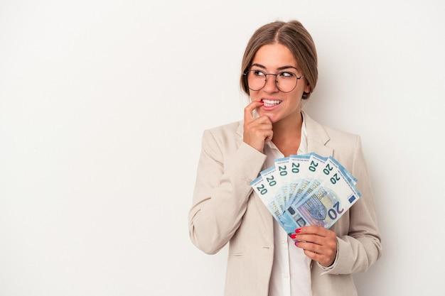 白い背景で隔離の紙幣を保持している若いロシアのビジネス女性は、コピースペースを見ている何かについて考えてリラックスしました。