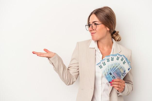 手のひらにコピースペースを示し、腰に別の手を保持している白い背景で隔離の紙幣を保持している若いロシアのビジネス女性。
