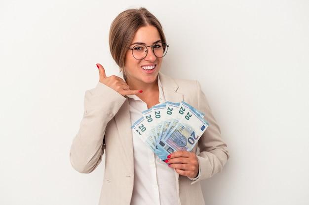 指で携帯電話の呼び出しジェスチャーを示す白い背景で隔離の紙幣を保持している若いロシアのビジネス女性。